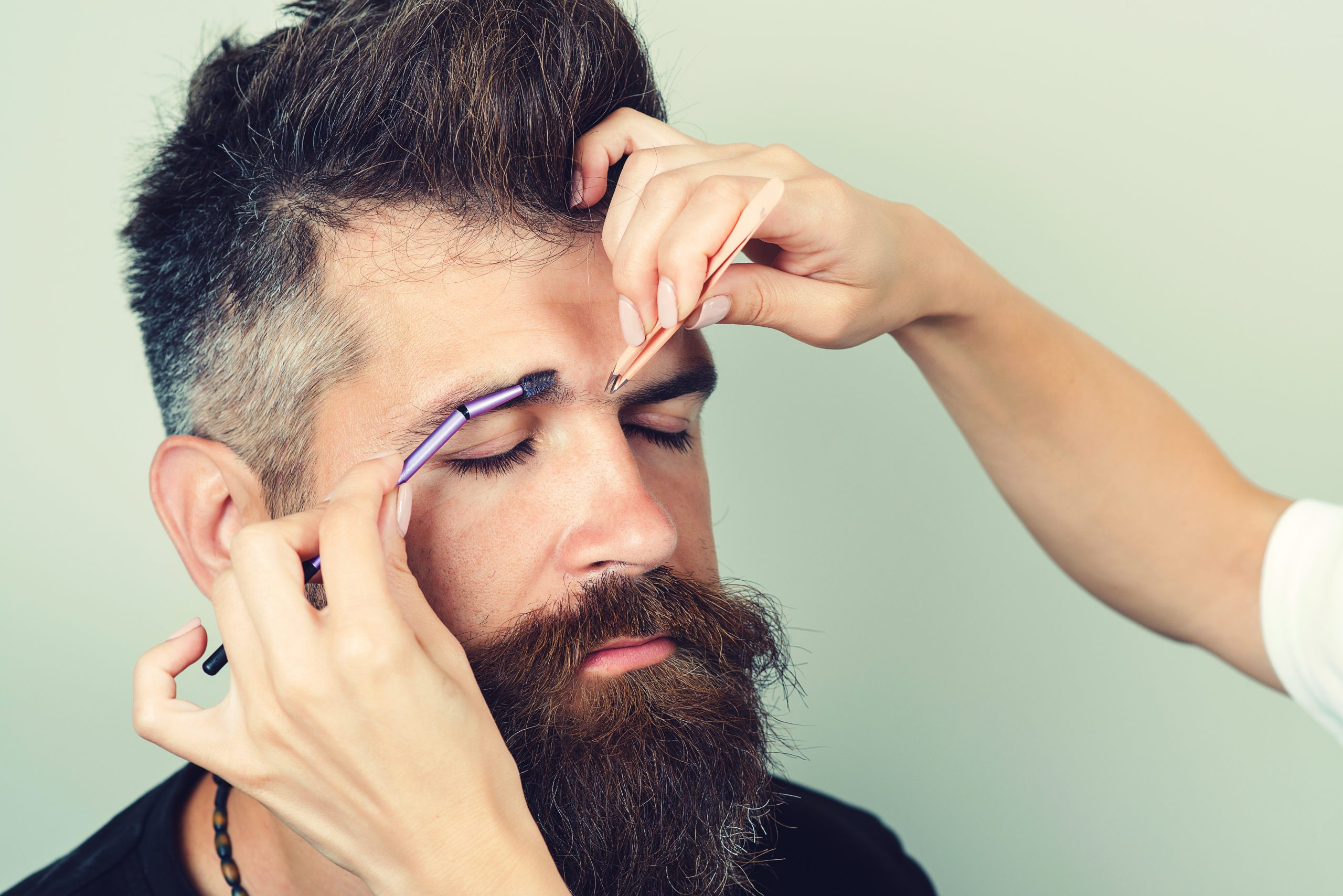 Beautician plucking handsome beautiful bearded man eyebrows with tweezers in beauty salon. Painful procedure. Unhappy brutal man with beard feeling pain while plucking his eyebrows. Beauty and fashion